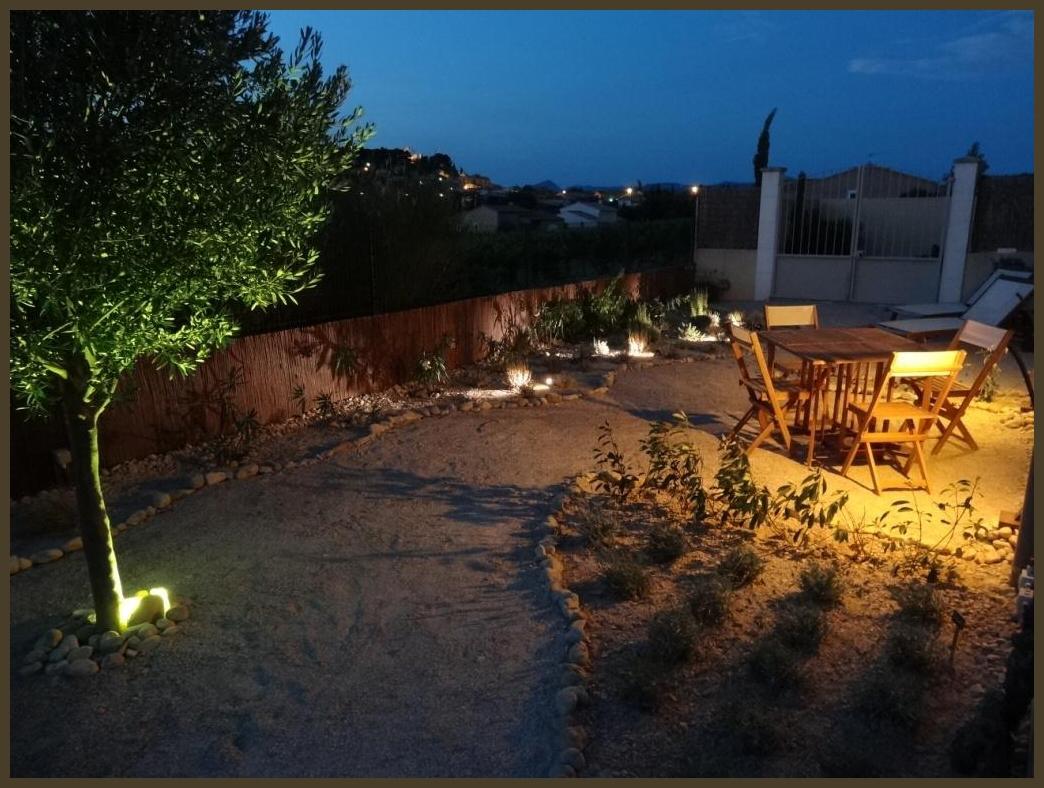 De sfeervol verlichte tuin, met Rasteau op de achtergrond